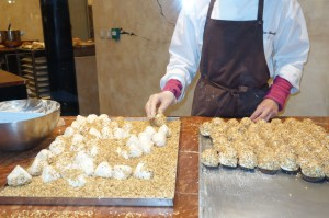 """Merveilleux"" being rolled in nuts at Aux Merveilleux de Fred"